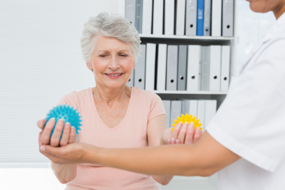 caregiver with senior patient using stress buster balls at the medical office