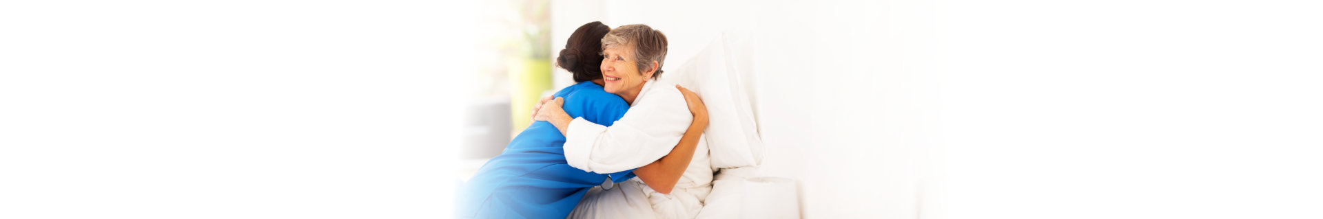 happy elderly woman hugging caregiver on bed